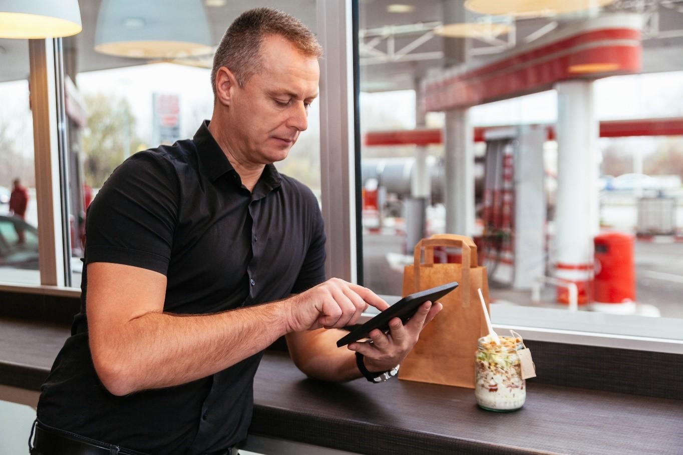 Homem branco no interior de uma loja de conveniência, com um dos braços apoiados em um balcão enquanto utiliza um tablet. Ao fundo, através de uma janela, um posto de gasolina.