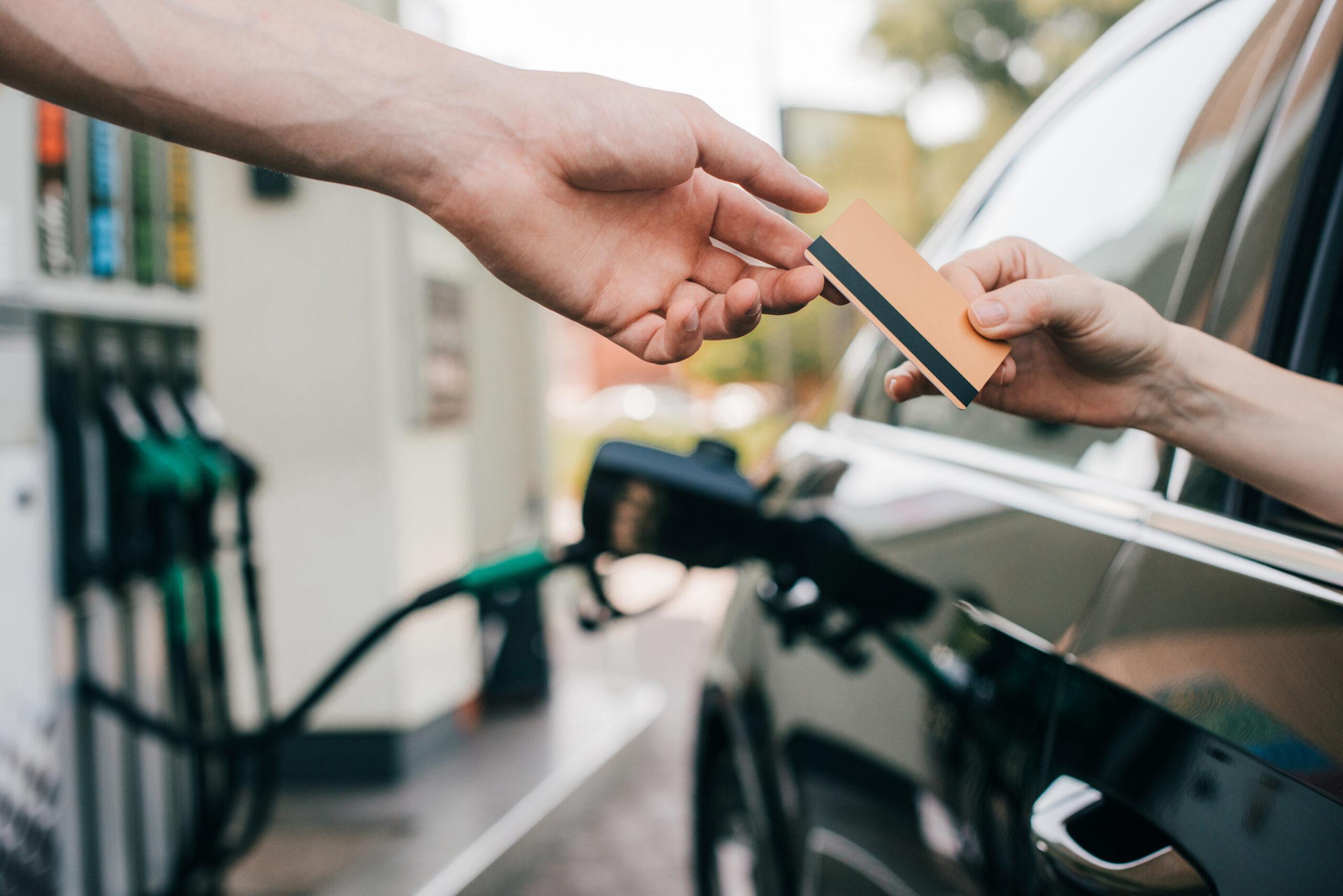 Cliente entrega cartão de pagamento ao colaborador de um posto de combustível