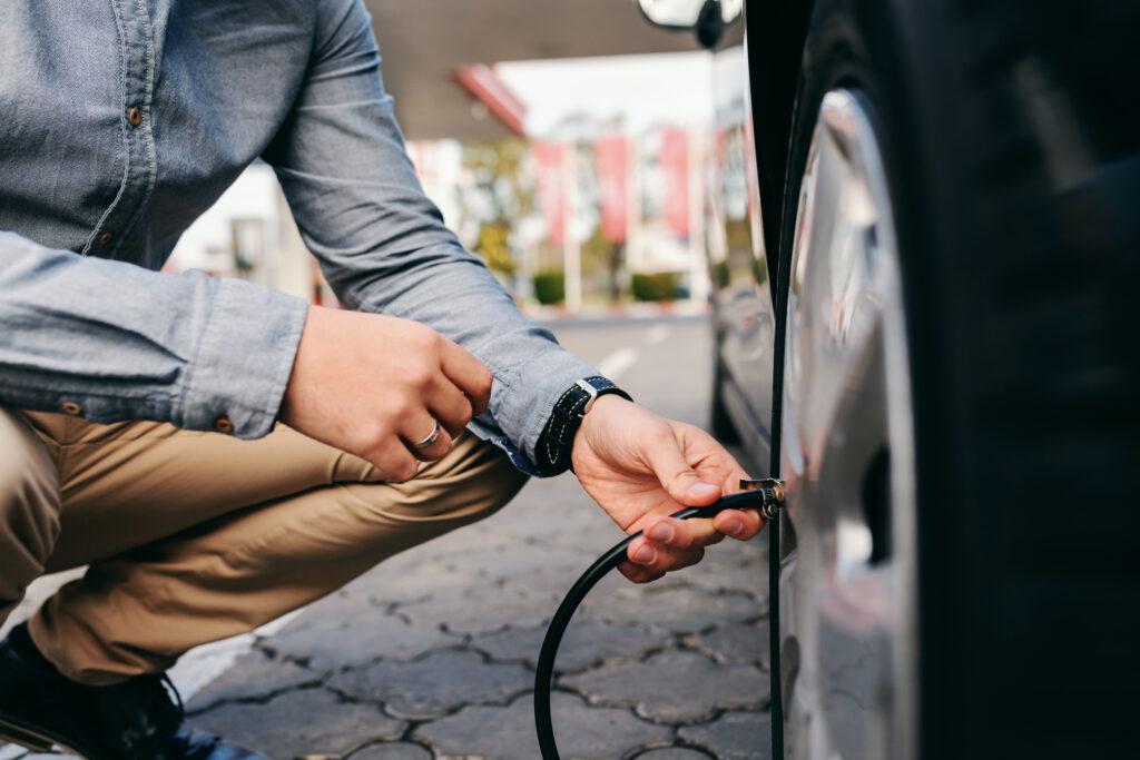 Homem abaixado próximo à roda de um carro, segurando uma mangueira de calibrador para pneus.